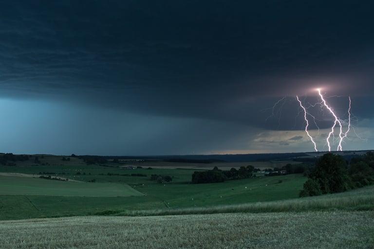Vertakte cg-bliksem in het heuvellandschap van Saint-Laurent-sur-Othain tijdens het blauwe uur.
