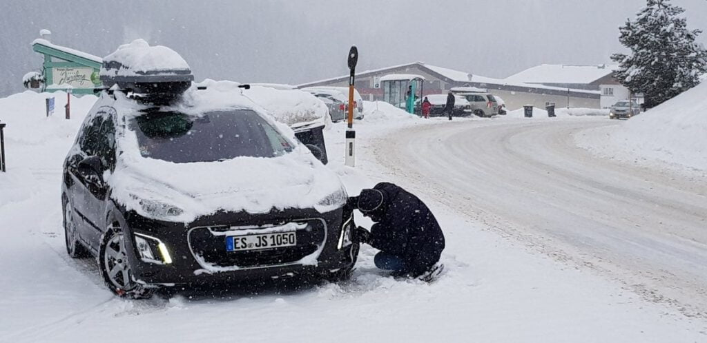 Sneeuwkettingen leggen, een must momenteel in een groot deel van de Alpen.